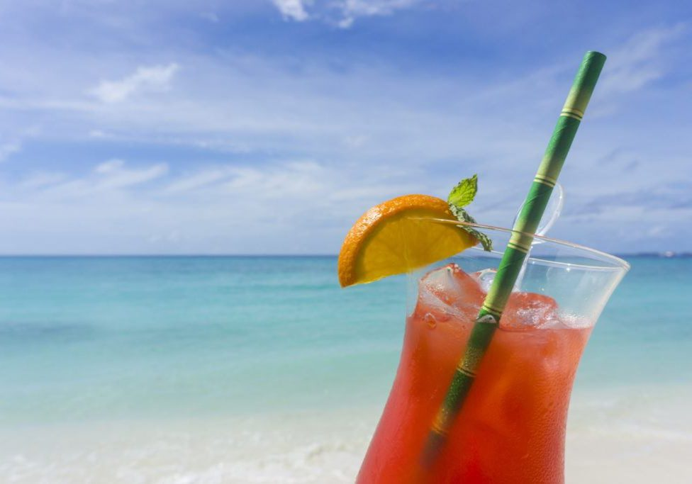 Summer cocktail against tropical sea and sky background